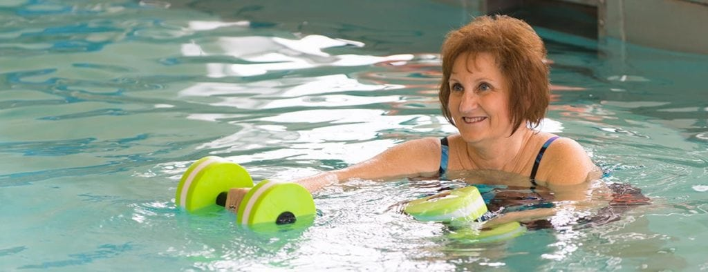 senior woman exercising in a pool at otterbein